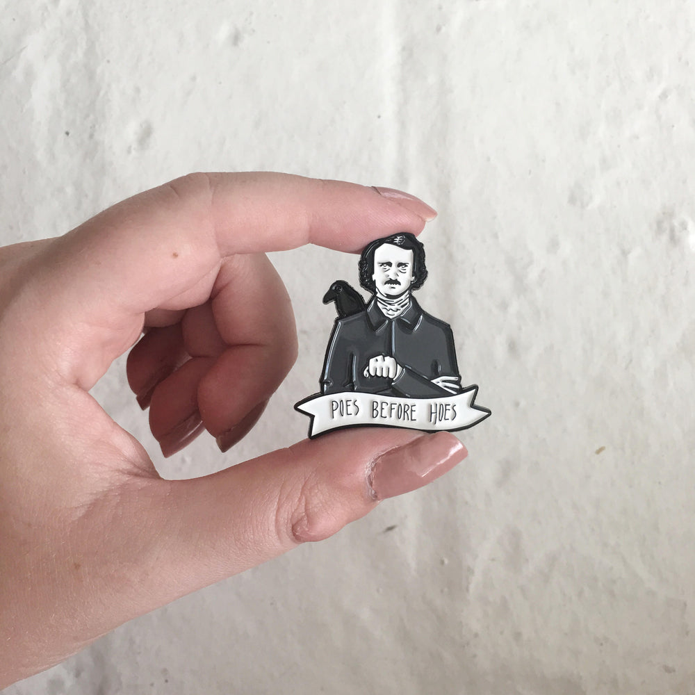 An enamel pin of Edgar Allen Poe measuring 39.7mm x 38mm.
