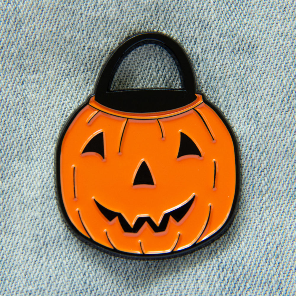 A cute jack-o-lantern enamel pin for spooky season fashion.
