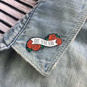 "A floral enamel pin of a banner with the quote, ""Que Sera, Sera,"" which means, ""What will be, will be."" The Accessory is pictured on the lapel of a denim jacket."