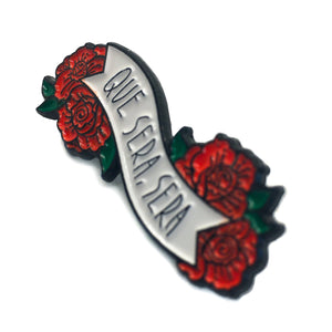 "A side view of a soft enamel pin of red flowers around a white banner with the quote, ""Que Sera, Sera"" for women's fashion."
