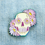 A holographic rainbow enamel pin of a human skull surrounded by flowers.