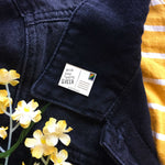 A black denim jacket with an LGBT pin on the lapel.