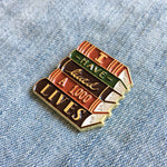 A beautiful, gold brooch of a stack of books with a literary quote for readers.