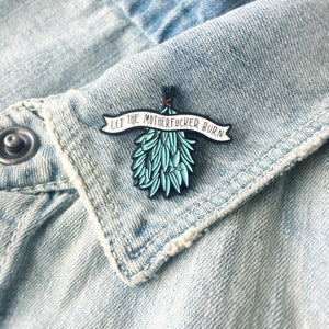 A spiritual healing pin on the lapel of a denim jacket.