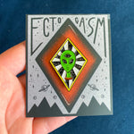 A space themed enamel pin of a green alien with a third eye for paranormal inspired fashion.