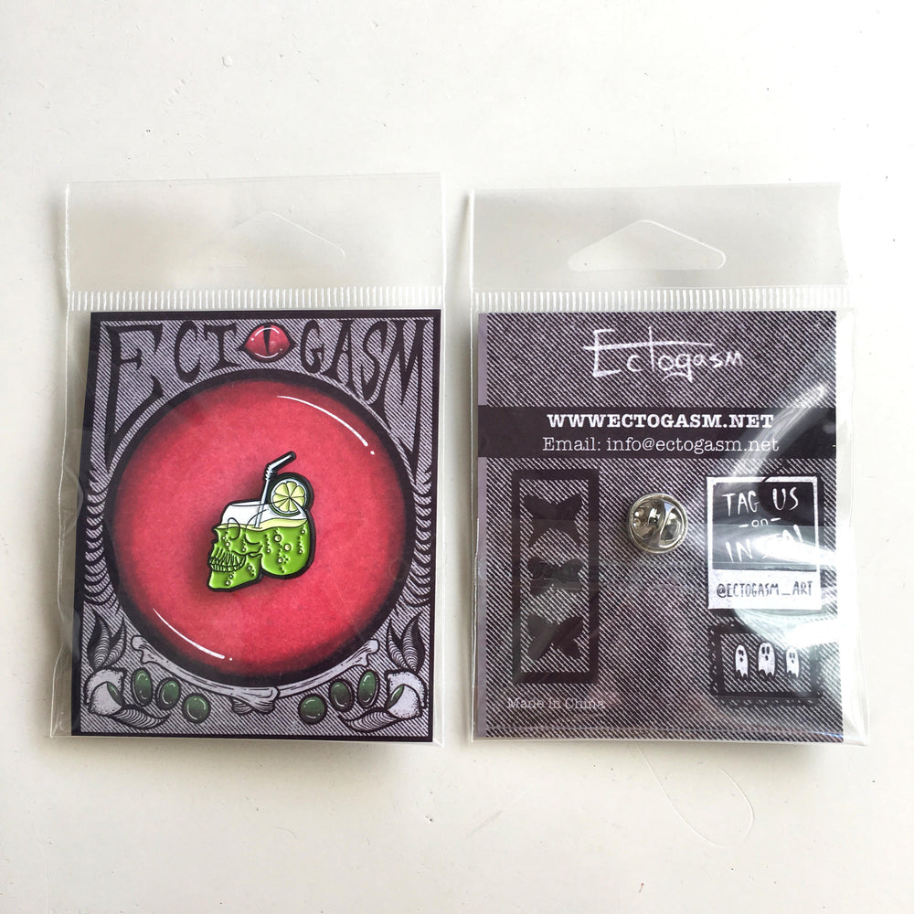 A skull cocktail enamel pin on spooky, Halloween themed packaging.