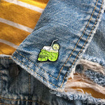 A creepy, horror themed enamel pin of an alcoholic drink shaped like a skull. Pictured on a the lapel of a men's denim jacket.