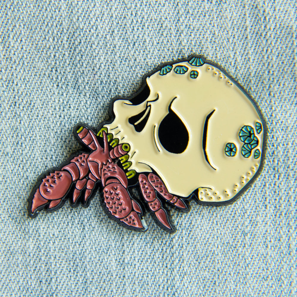 A nautical horror enamel pin of a hermit crab with a human skull for its shell.