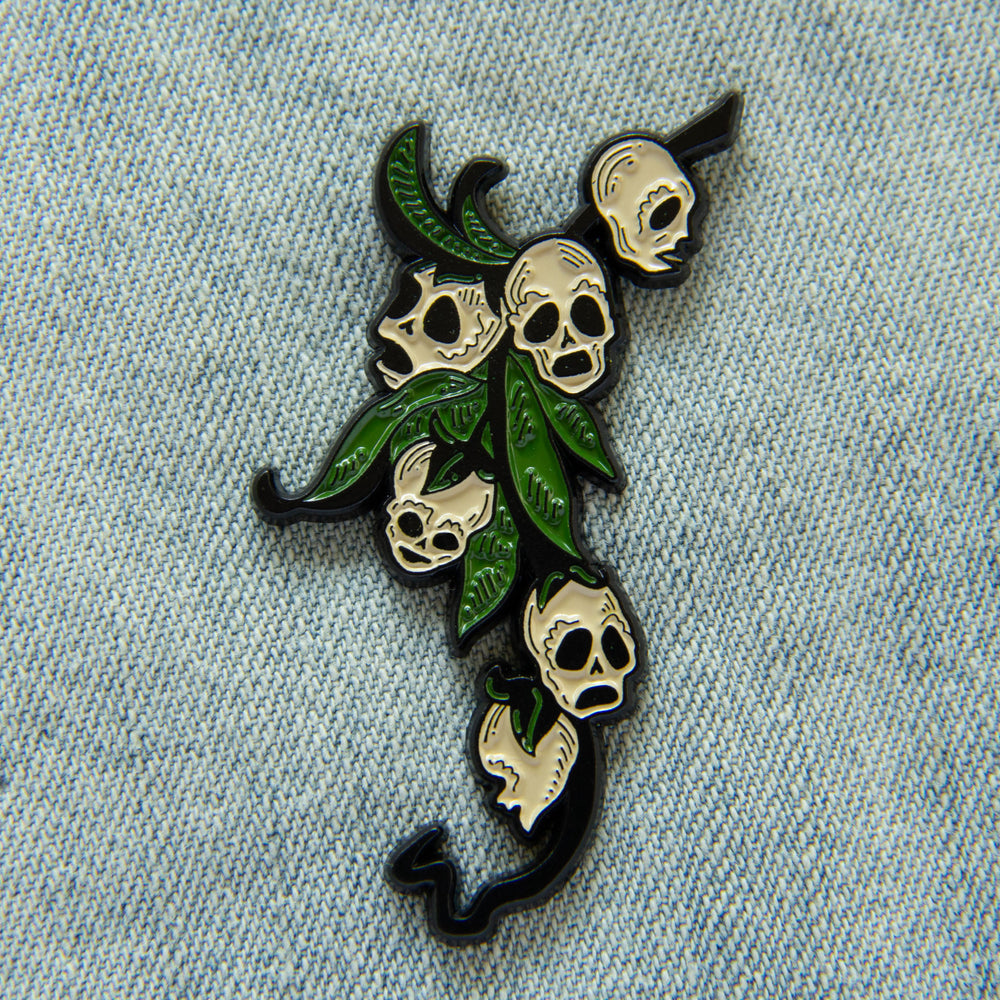 A witchy enamel pin of the snapdragon skull plant.