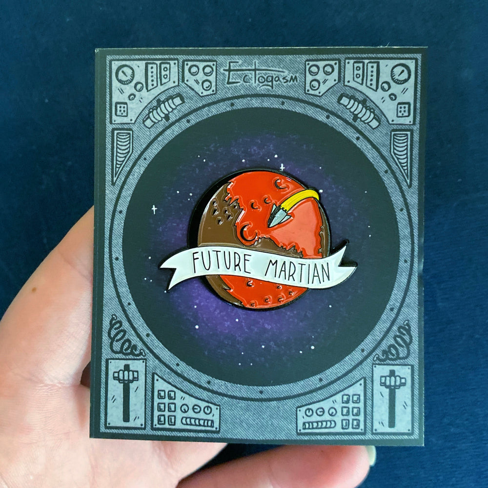 A collectible Mars planet enamel pin on a spaceship themed art card.