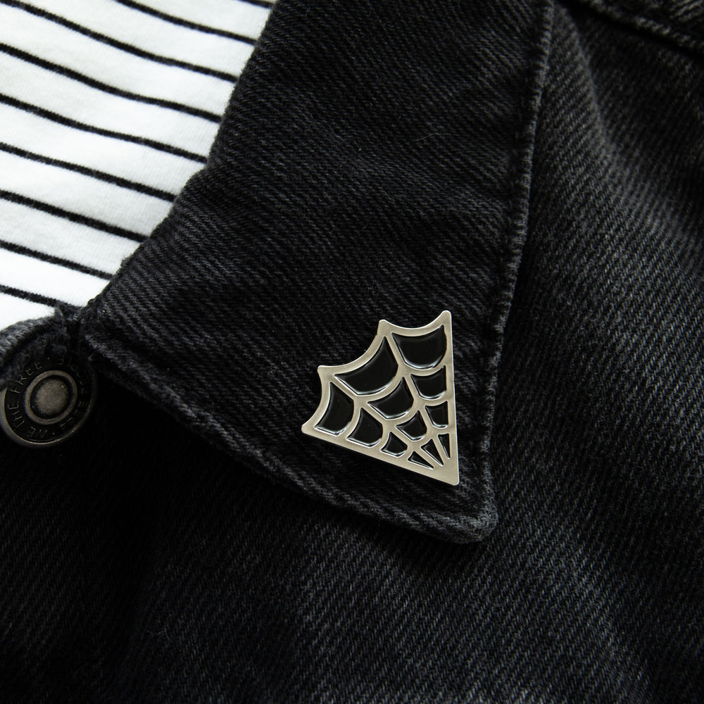 An enamel pin of a silver and black cobweb on the lapel of a denim jacket for witchy style.