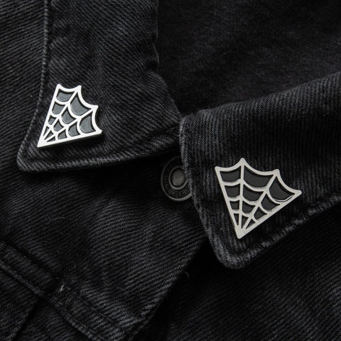 Black and silver cobweb collar pins.