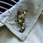 A spooky lapel pin of snapdragon skulls with leaves.