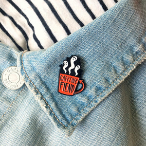 "Ectogasm's coffee cup ""Caffeine Fiend"" pin on the lapel of a denim jacket for cool unisex fashion."