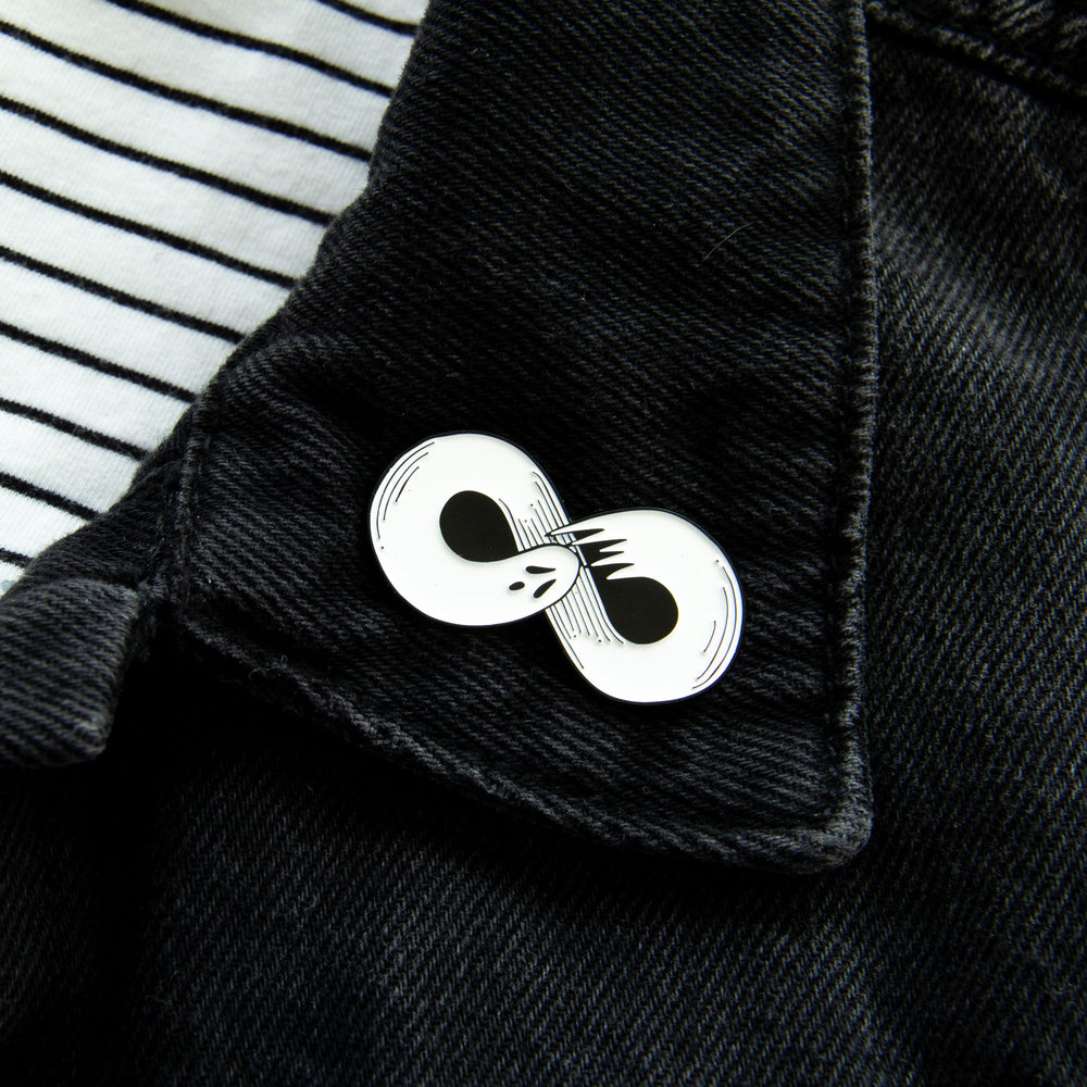 A horror pin of a ghost on the lapel of a black denim jacket for unisex adults.