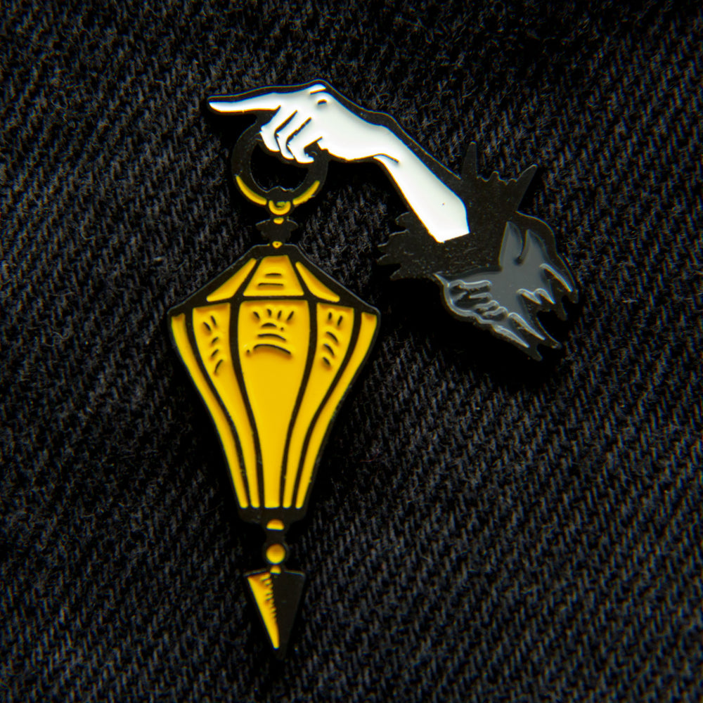 A victorian gothic enamel pin of a lantern and a hand pointing.