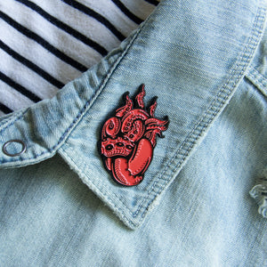 A tentacle enamel pin for unisex punk fashion.