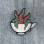 A cool enamel pin of a teacup with red and green tentacles coming out of it. Drawn in the woodcut style, it is an excellent accessory for nautical fashion.