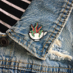 A cool tentacle and teacup brooch on the lapel of a denim vest for punk style.