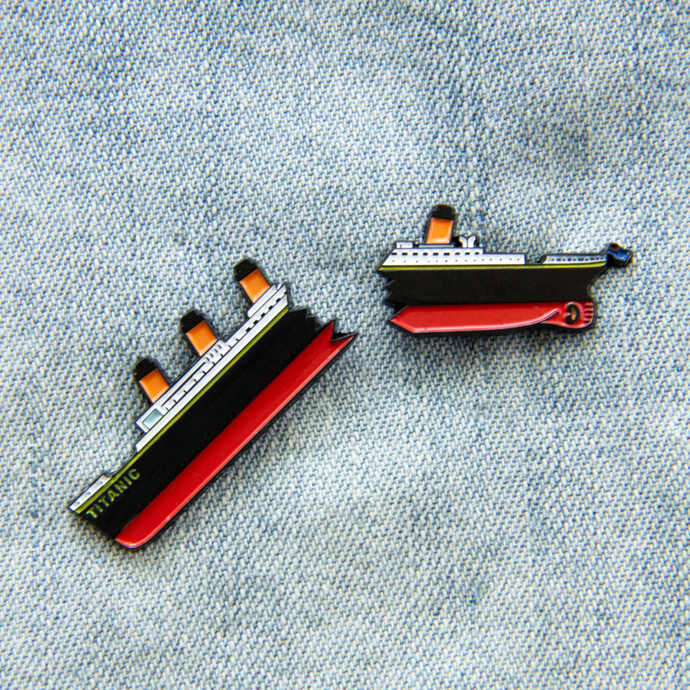A set of enamel pins that feature RMS Titanic in two broken halves.