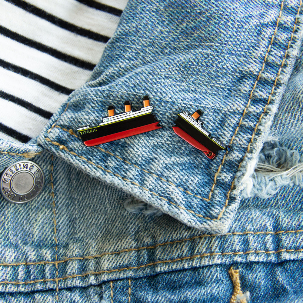 A nautical pin of RMS Titanic, sinking into the ocean. Pictured on the lapel of a denim jacket.