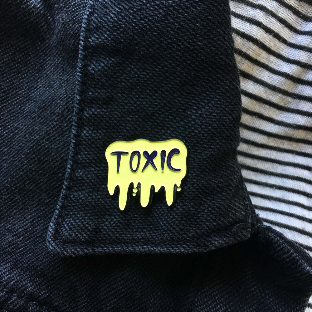 "A pin of the word, ""Toxic"" on the lapel of a black jacket for unisex fashion."