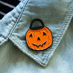 A cute trick or treat bucket enamel pin on the lapel of a denim jacket.