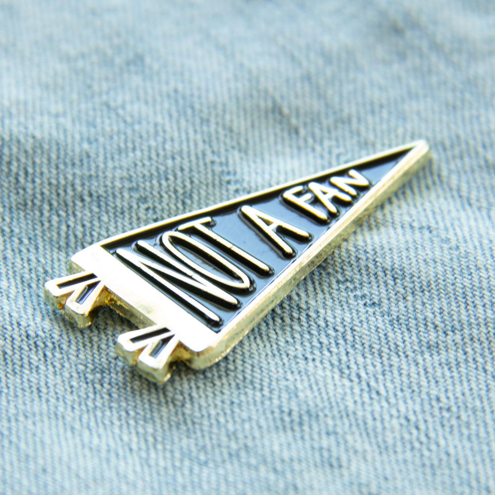 A gold enamel pin of a pennant flag with a funny quote for unisex grunge fashion.