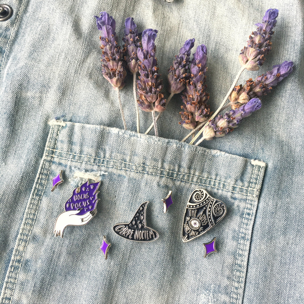 A cute outfit of a denim jacket with witchy lapel pins on the pocket.