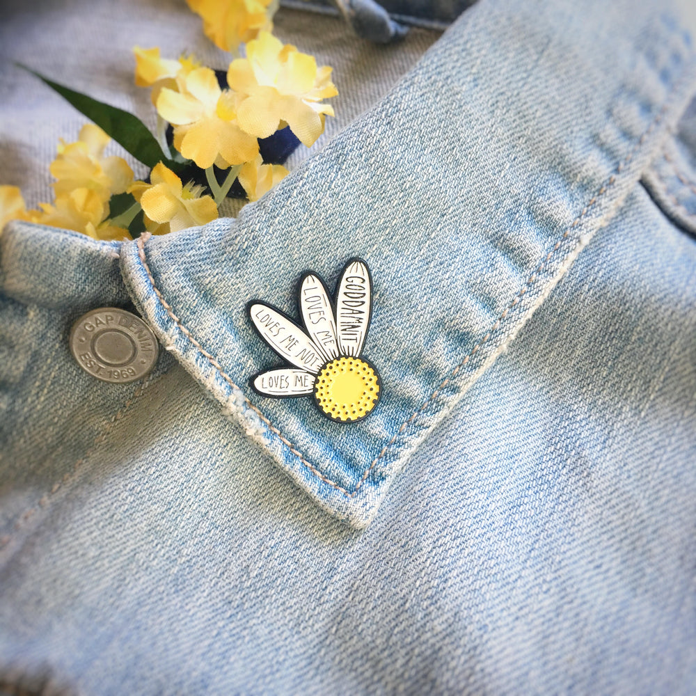 A cute enamel pin of a white and yellow flower with a funny quote on it. It is pinned to the lapel of a jean jacket.
