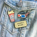 A collection of funny, movie theater themed enamel pins.