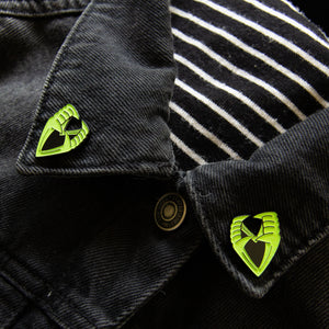 Glow-in-the-dark vampire teeth enamel pins on the collar points of a jacket.
