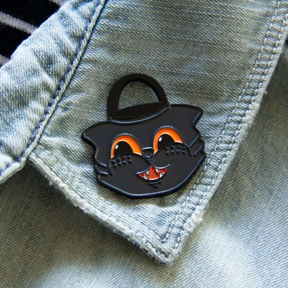 A retro black cat enamel pin on the lapel of a denim jacket for fall fashion.