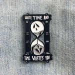 "A spooky enamel pin of an hourglass with ghost faces on it. On the top and bottom is the Shakespeare inspired quote, ""waste time and time wastes you""."