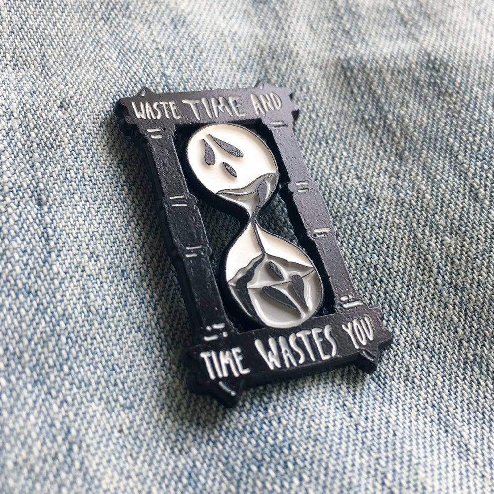 A spooky, goth style lapel pin designed by Ectogasm. It is made from black plated metal with a white and gray enamel fill.