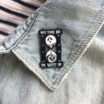 A ghostly, black enamel pin on a denim jacket lapel for punk fashion.