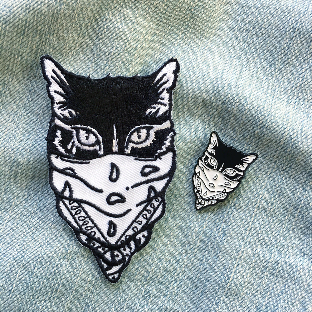 A matching black and white cat enamel pin and patch set, designed by Ectogasm in California.