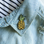 A cool enamel pin of a pineapple with spooky eyes. Made with black metal and yellow enamel.