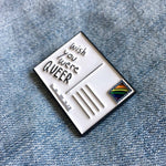 "A lapel pin of a rainbow postcard with the funny quote, ""Wish You Were Queer""."