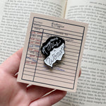 A book themed enamel pin of a feminist author's quote.