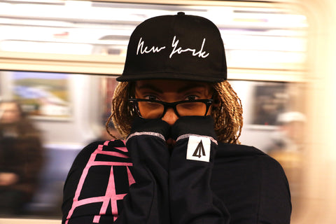 Trademark Lines Long Sleeve and New York Script Snapback in the Underground of NYC