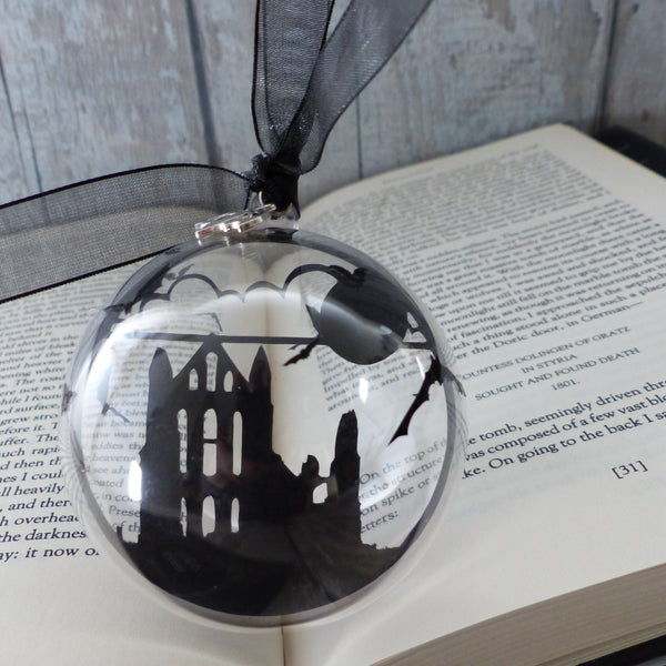 black paper cut of Whitby abbey encased in plastic bubble decorated with bats