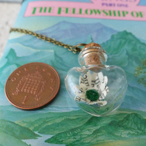 Book daisy in bottle next to 1 pence piece for scale
