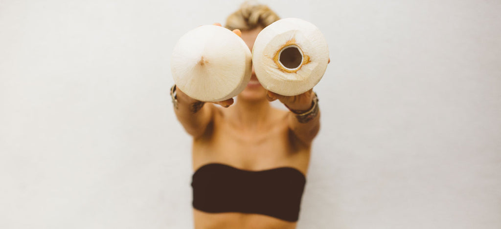 Meredith Baird Figone holding coconuts toward camera against a white background