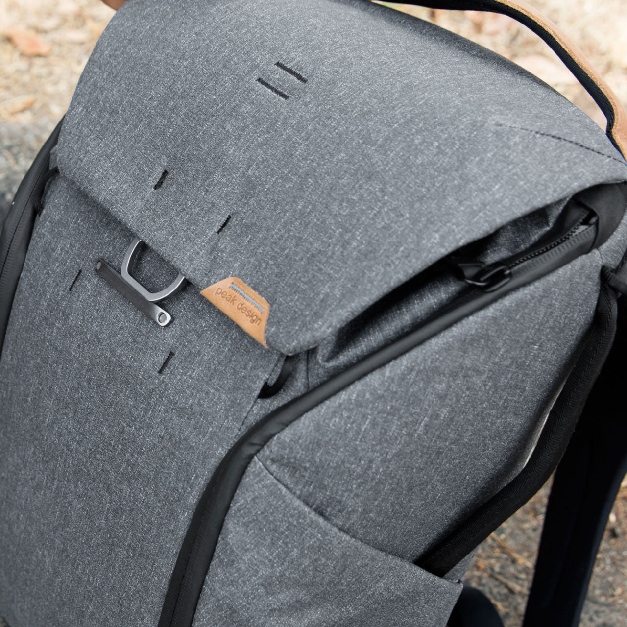 Man opening side zipper of Everyday Backpack