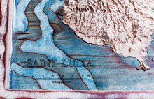 Close up of the 3D wood map of Saint Lucia in the Caribbean Sea. True elevation data. Sea is hand painted in blue.