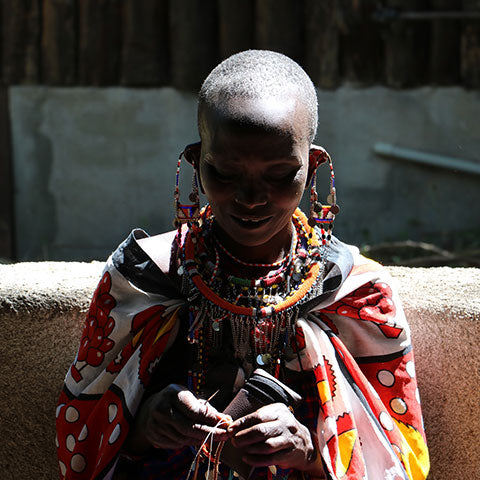 A highly focused Maasai woman in an African dress wearing handmade jewelry.