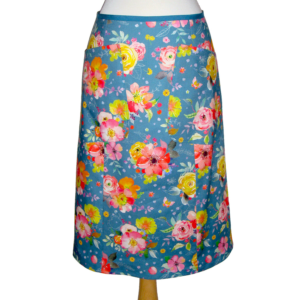 Midi Cotton skirt in a vintage floral print with large patch pockets. Flowers are yellow red and pink over a teal background.