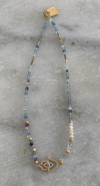 Fluorite and Pearl choker necklace in gold with a hand .
