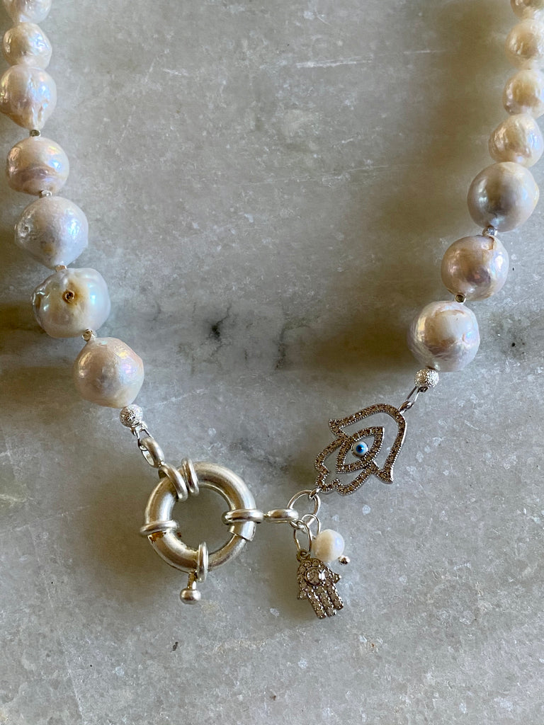Pearl necklace with silver Hamsa pendants